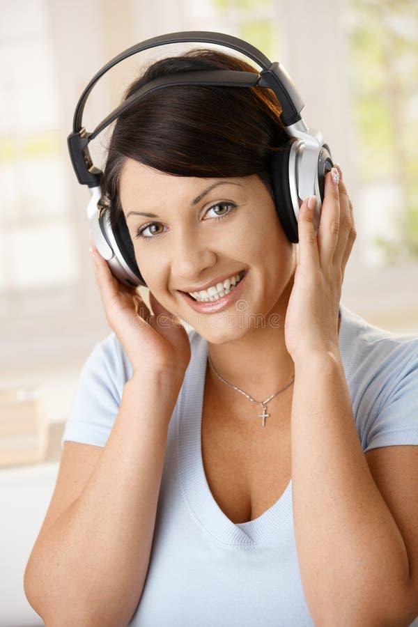 Gelukkige vrouw die van muziek op hoofdtelefoons geniet stock afbeelding