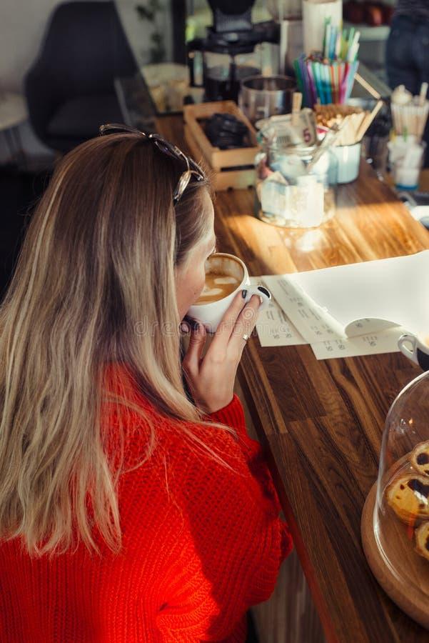 Gelukkige vrouw die van wat koffie in een cafetaria genieten stock foto's