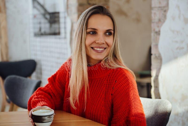 Gelukkige vrouw die van wat koffie in een restaurant genieten stock afbeeldingen