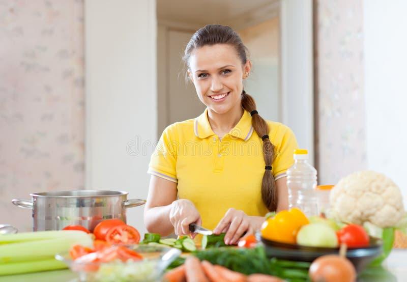 Gelukkige vrouw die vegetarische salade koken stock afbeeldingen