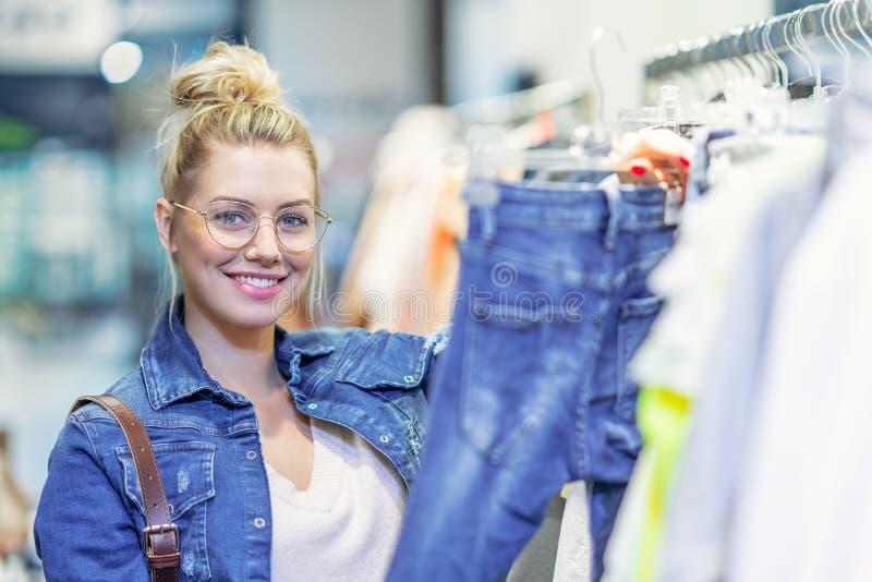 Gelukkige vrouw die voor kleren in opslag winkelen stock afbeeldingen
