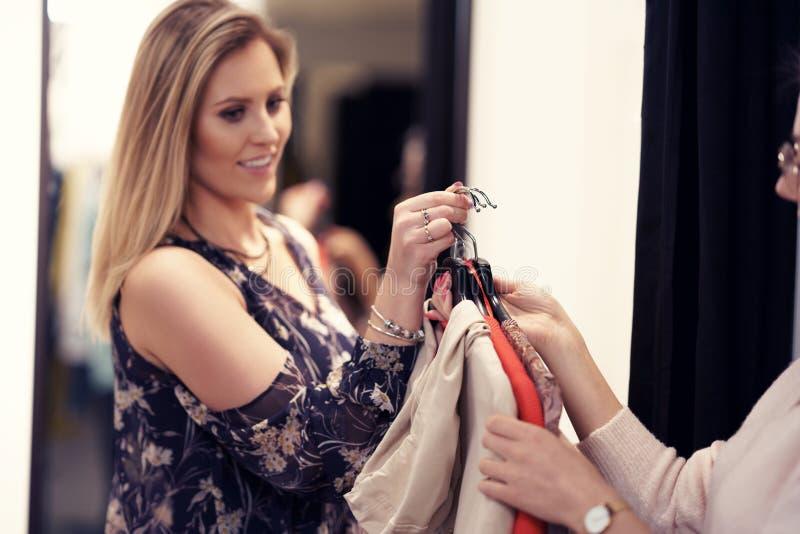 Gelukkige vrouw die voor kleren in opslag winkelen stock afbeelding