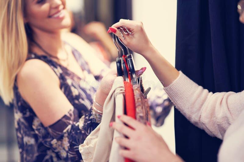 Gelukkige vrouw die voor kleren in opslag winkelen royalty-vrije stock fotografie