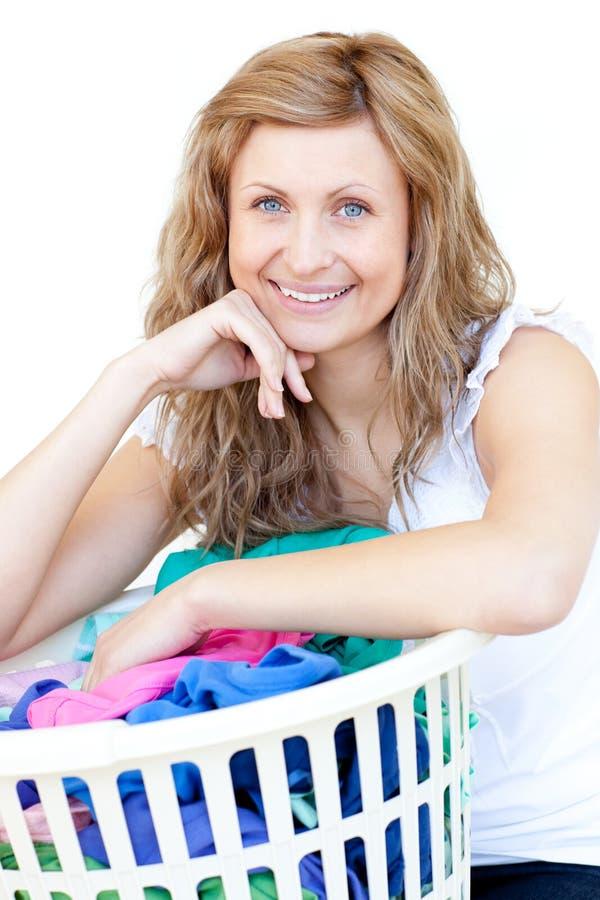 Gelukkige vrouw die wasserij doet stock afbeelding