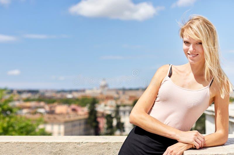Gelukkige vrouw die zich bij balkon in de zomer bevinden stock foto