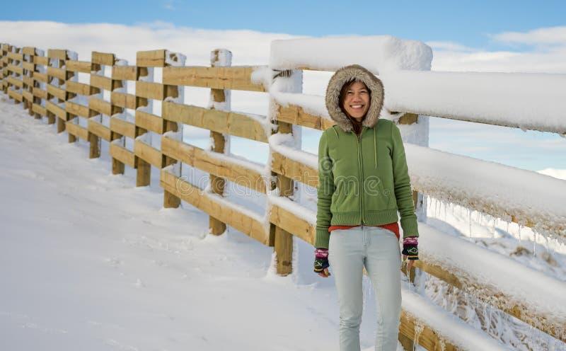 Gelukkige vrouw die zich bij skigebied dichtbij houten omheining bevinden stock afbeelding
