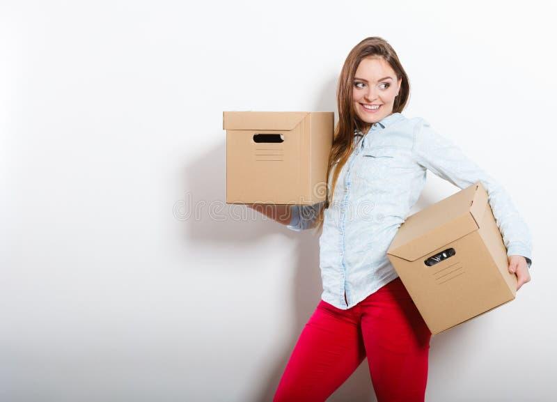 Gelukkige vrouw die zich in huis dragende dozen bewegen stock afbeeldingen