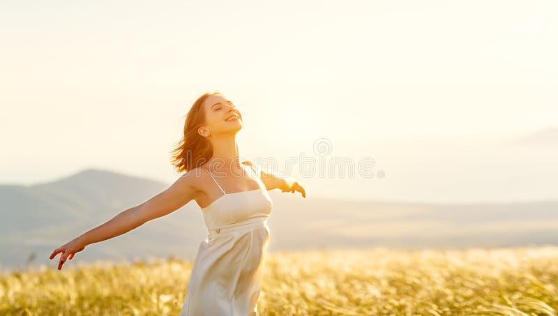 Gelukkige vrouw die zich met haar terug op zonsondergang in aard bevinden iwith ope royalty-vrije stock afbeelding