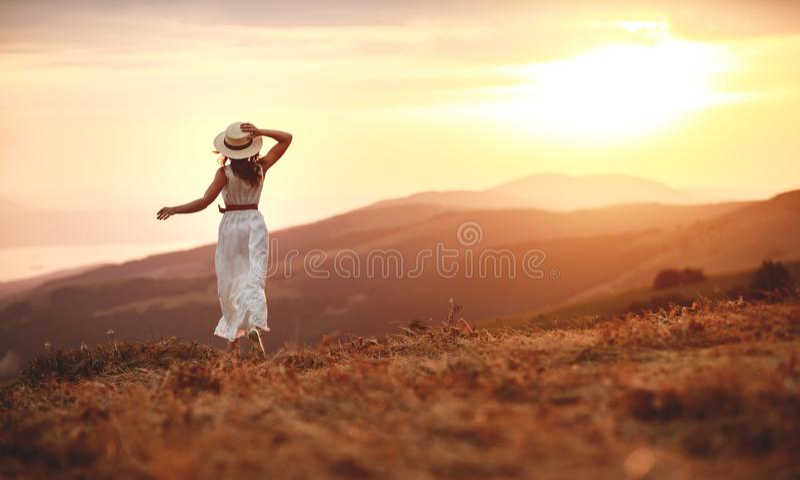Gelukkige vrouw die zich met haar terug op zonsondergang in aard iwith open handen bevinden royalty-vrije stock foto