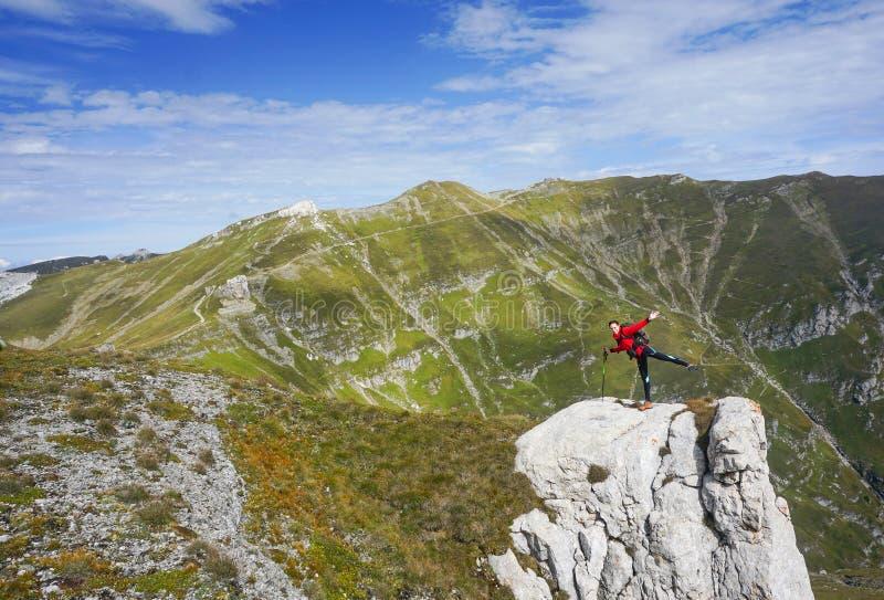 Gelukkige vrouw die zich op één been op een klip in de bergen bevinden stock afbeeldingen
