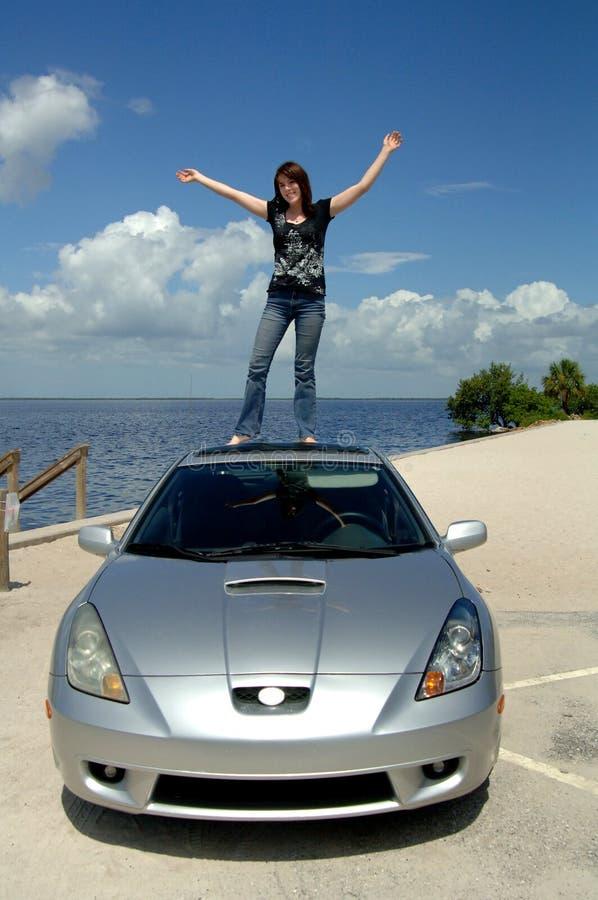 Gelukkige vrouw die zich op dak van auto bevindt stock foto's