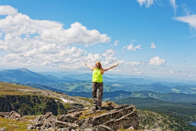 Gelukkige vrouw die zich op rots bevinden royalty-vrije stock foto