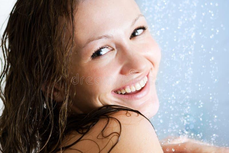 Gelukkige vrouw in douche stock foto's