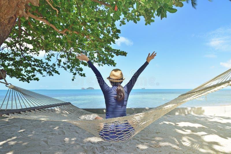 Gelukkige vrouw in een hangmat die van vakantie op strand genieten stock fotografie