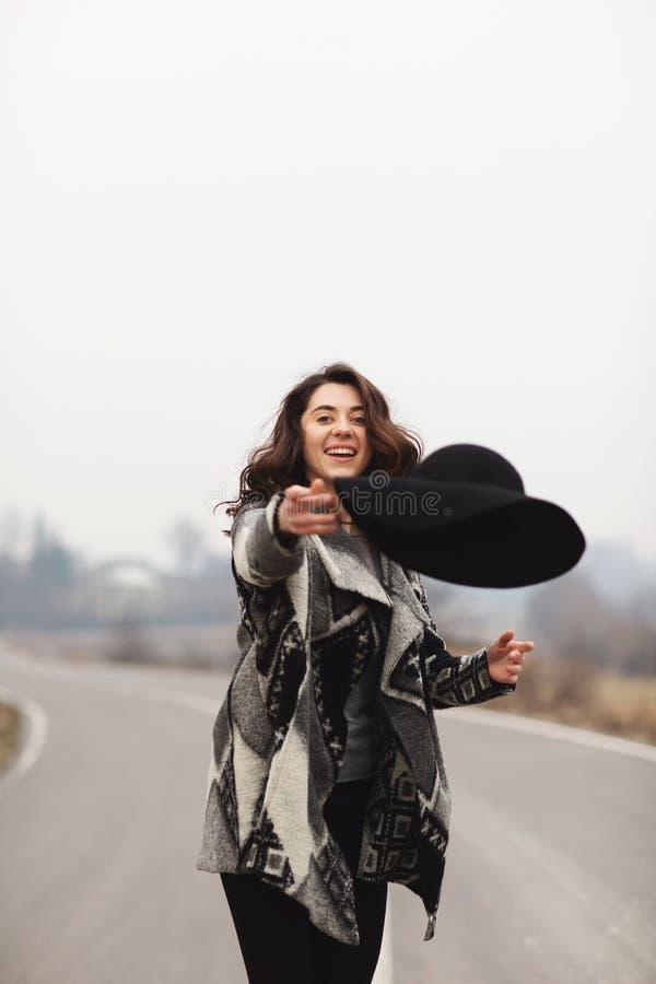 Gelukkige vrouw in een mooie grijze cardigan en zwarte hoedenritten langs de manier royalty-vrije stock afbeeldingen