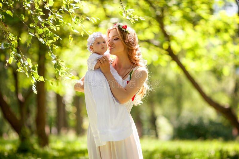 Gelukkige vrouw en baby in de de zomertuin De vakantieconcept van de moedersdag royalty-vrije stock fotografie