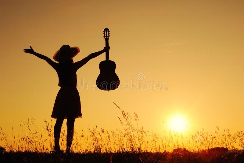 Gelukkige vrouw en gitaar met zonsondergangsilhouet stock foto