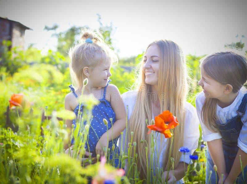 Gelukkige vrouw en haar dochters in de bloeiende de lentetuin stock foto