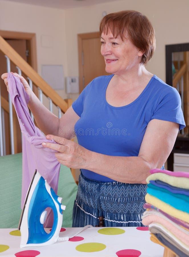 Gelukkige vrouw en het strijken stock foto