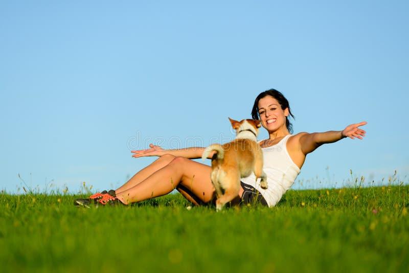 Gelukkige vrouw en weinig hond die pret hebben royalty-vrije stock afbeeldingen