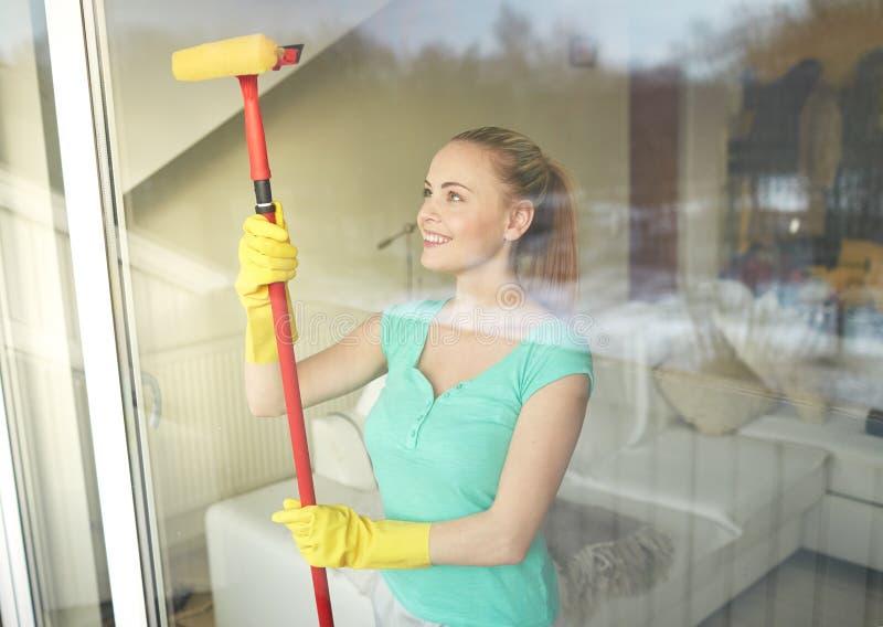 Gelukkige vrouw in handschoenen die venster met spons schoonmaken royalty-vrije stock fotografie