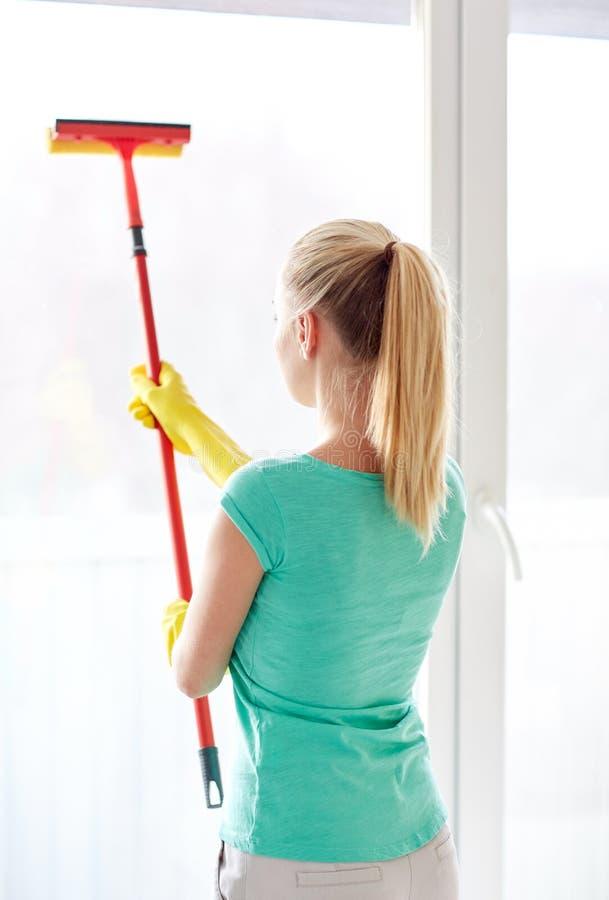 Gelukkige vrouw in handschoenen die venster met spons schoonmaken stock afbeelding