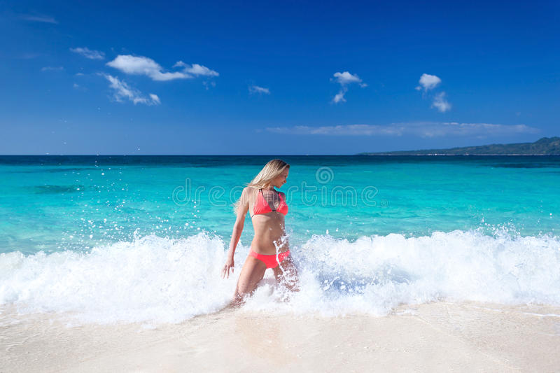 Gelukkige vrouw in heldere bikini op strand stock afbeeldingen