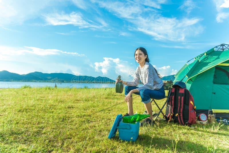 Gelukkige vrouw het drinken alcohol terwijl het kamperen bij weide Mensen en levensstijlenconcept Reis en avonturenthema Vrouweli stock foto