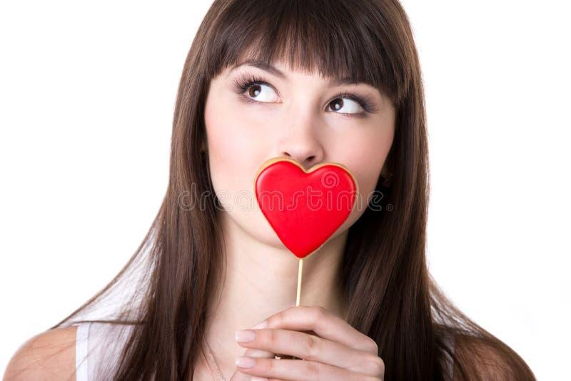 Gelukkige vrouw in het gevormde koekje van de liefdeholding hart stock foto's