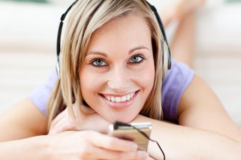 Gelukkige vrouw het luisteren muziek die op de vloer ligt stock afbeelding