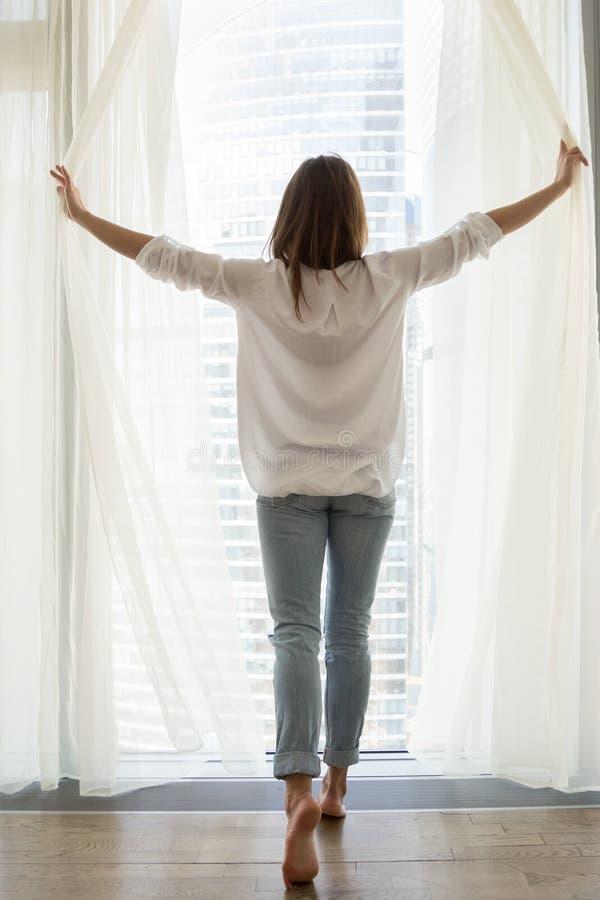 Gelukkige vrouw het openen gordijnen die van mening van venster genieten stock foto