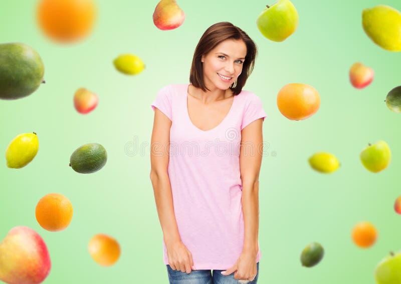 Gelukkige vrouw in lege witte t-shirt over vruchten royalty-vrije stock afbeelding
