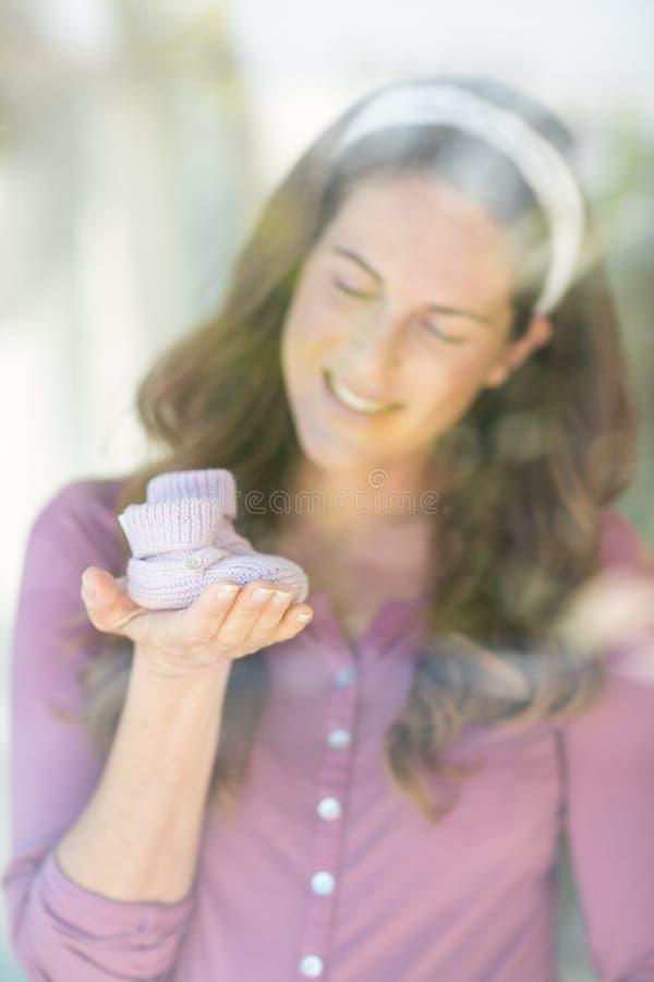 Gelukkige vrouw met babyschoenen royalty-vrije stock afbeeldingen