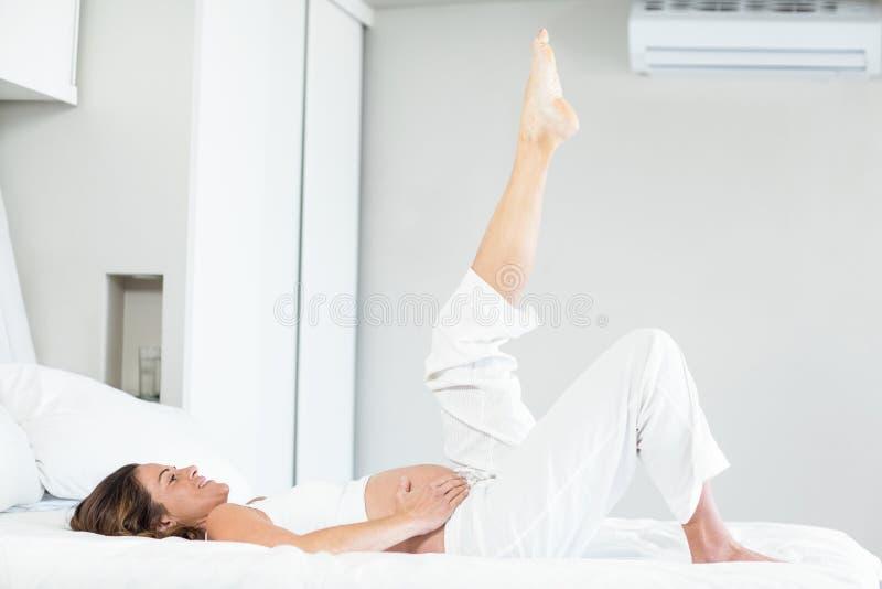 Gelukkige vrouw met been omhoog op bed royalty-vrije stock foto