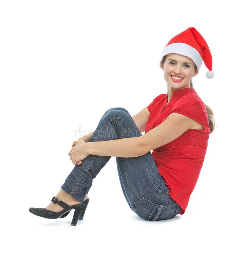 Gelukkige vrouw met de hoedenzitting van Kerstmis op vloer royalty-vrije stock foto