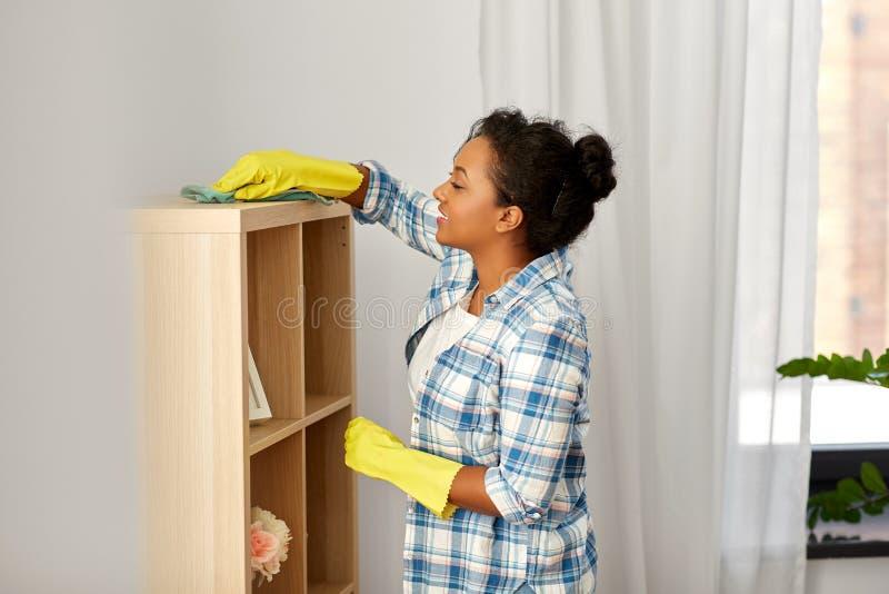 Gelukkige vrouw met doek die rek thuis bestrooien stock afbeeldingen