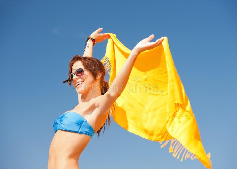 Gelukkige vrouw met gele sarongen op het strand stock foto's