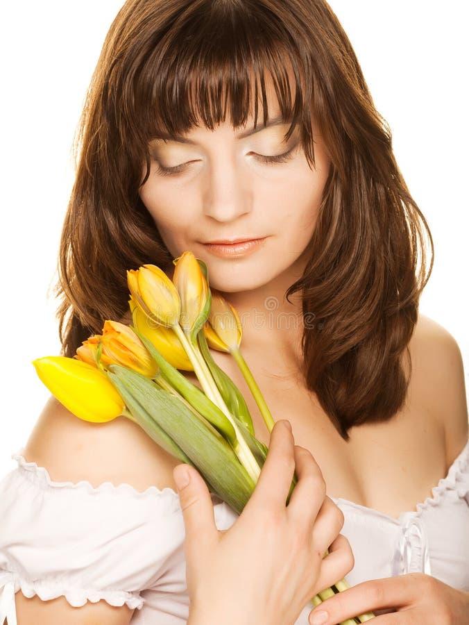 Gelukkige vrouw met gele tulpen over wit royalty-vrije stock foto