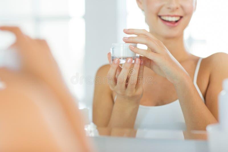 Gelukkige vrouw met gezichtsroom bij badkamers stock fotografie