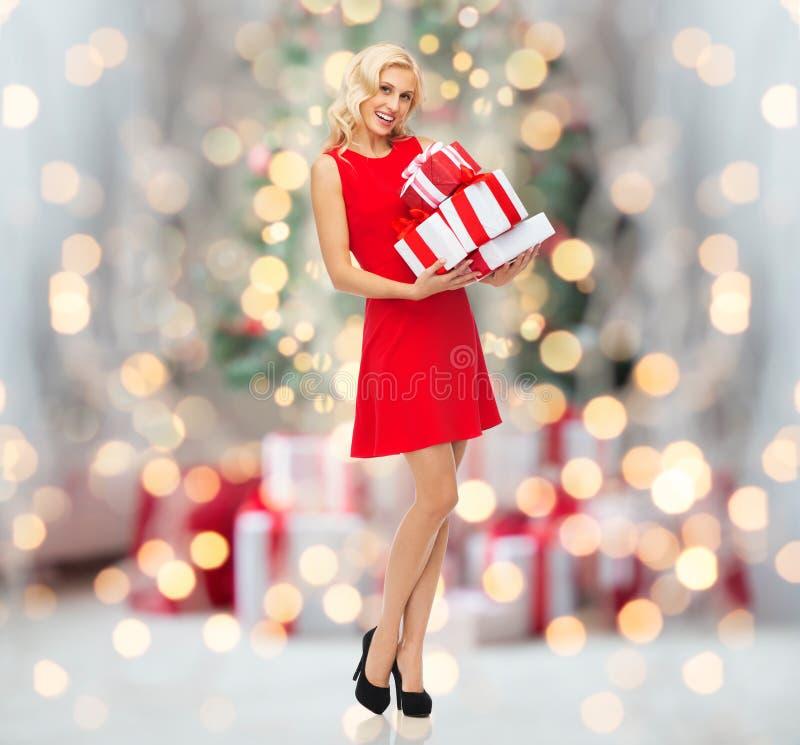 Gelukkige vrouw met giftdozen over Kerstmislichten stock afbeelding