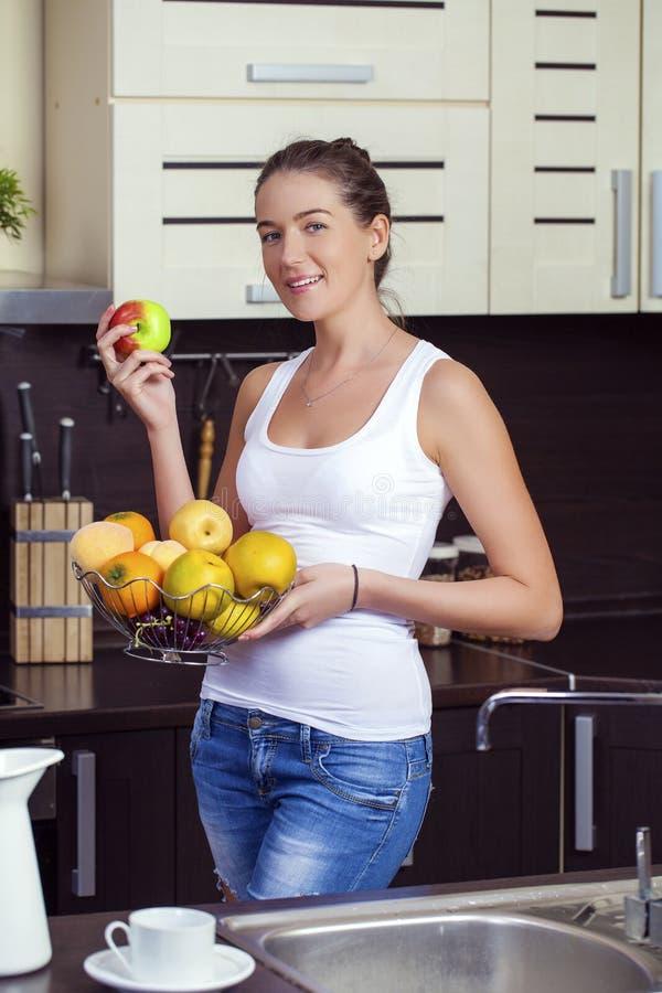 Gelukkige vrouw met groene appelen op een plaat op keuken stock foto's