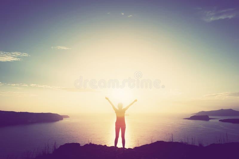 Gelukkige vrouw met handen omhoog op klip over overzees en eilanden bij zonsondergang royalty-vrije stock afbeelding