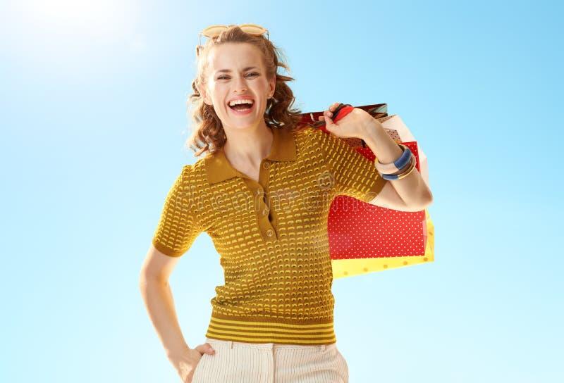 Gelukkige in vrouw met het winkelen zakken tegen blauwe hemel royalty-vrije stock afbeelding