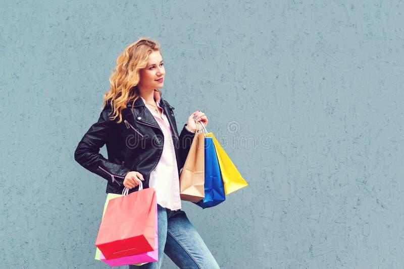 Gelukkige vrouw met het winkelen zakken tegen grijze muur Het winkelen tijd De ruimte van het exemplaar Consumentisme, het winkel royalty-vrije stock afbeelding
