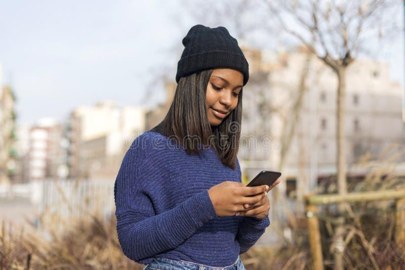 Gelukkige vrouw met hoed in stadsstraat, terwijl het gebruiken van technologie in openlucht, bewaarceltelefoon Zij is zwart, op h royalty-vrije stock afbeeldingen