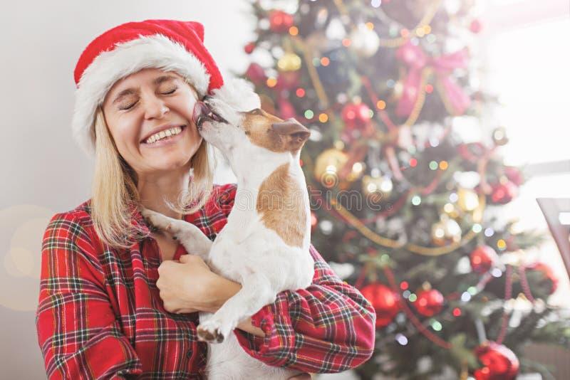 Gelukkige vrouw met hond in Kerstmisdecoratie stock afbeelding