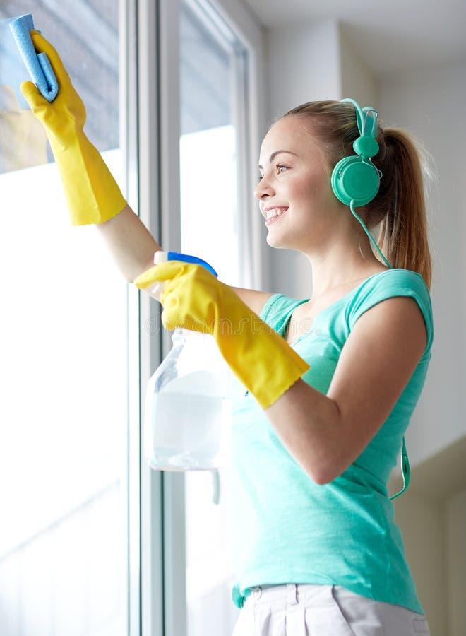 Gelukkige vrouw met hoofdtelefoons die venster schoonmaken stock afbeelding
