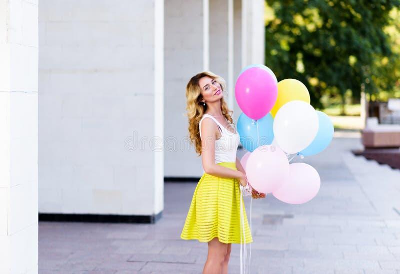 Gelukkige vrouw met kleurrijke ballons stock foto