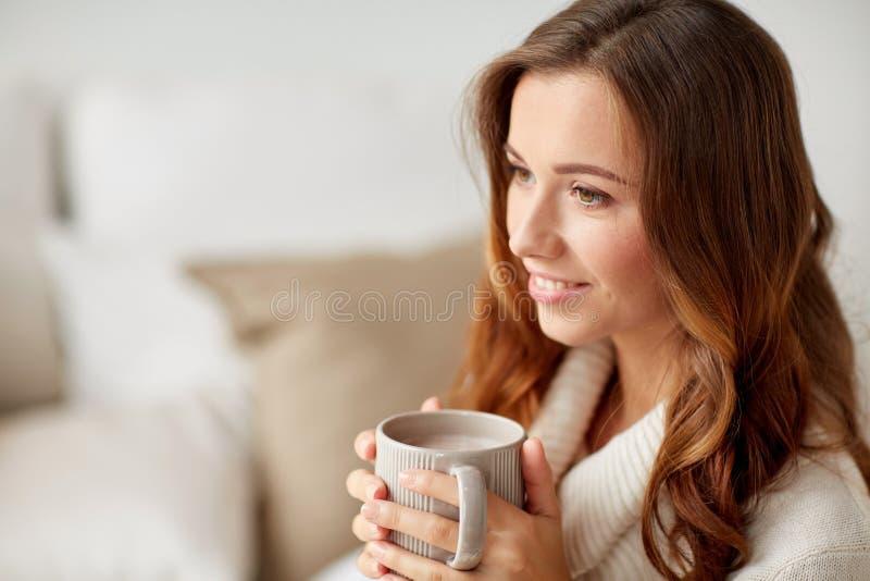 Gelukkige vrouw met kop van cacao of koffie thuis royalty-vrije stock fotografie