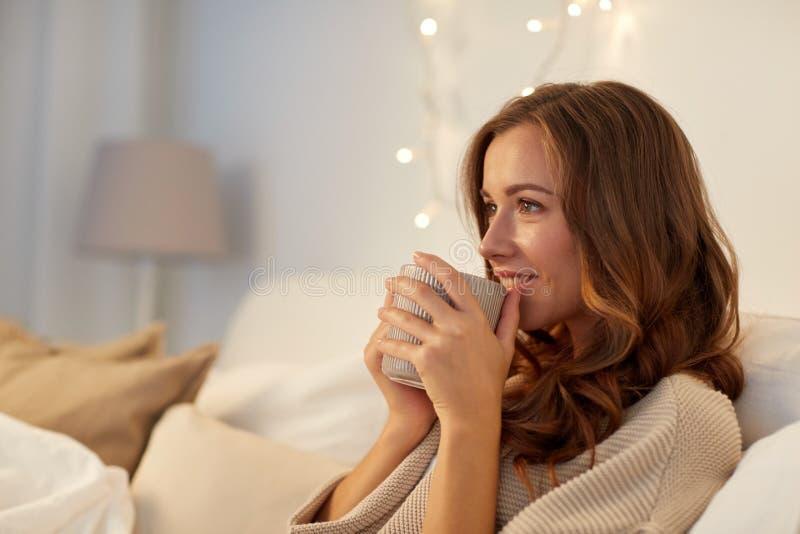 Gelukkige vrouw met kop van koffie in bed thuis stock afbeeldingen